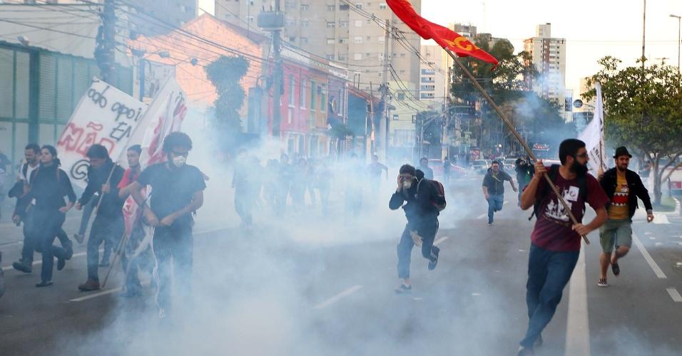 9.jun.2014 - Grevistas correm após a Tropa de Choque lançar bombas de gás lacrimogêneo durante protesto em frente a estação Ana Rosa, da linha 1-azul do metrô, durante a paralisação dos metroviários em São Paulo. Os metroviários votaram pela continuidade da greve após assembleia. Eles reivindicam reajuste salarial de 35,47%, mas chegaram a reduzir a exigência para 12,2%, índice que inclui a reposição da inflação de 7,98%, apurada pelo IGP-M da FGV, e aumento real