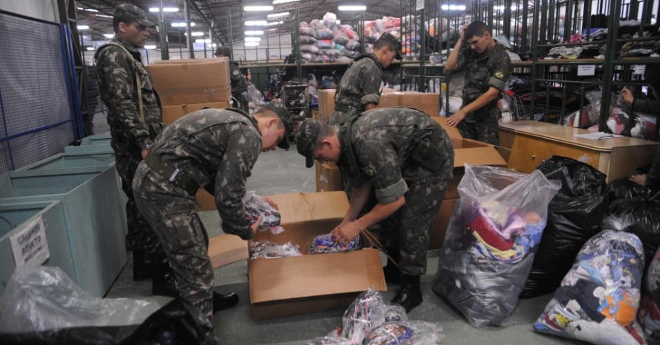 9.jun.2014 - Soldados do 27º Batalhão Logístico de Curitiba participam da triagem de doações feitas pela população da capital paranaense, nesta segunda-feira (9). Fortes chuvas causaram danos e deixaram centenas de famílias desabrigadas no Paraná