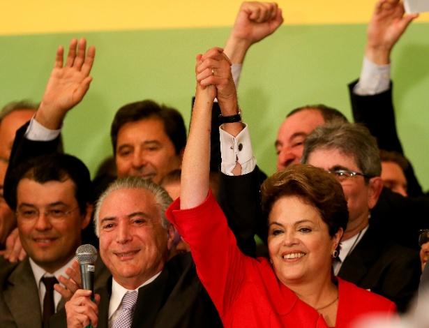 A então presidente Dilma Rousseff (PT-RS) segura mão do então vice-presidente Michel Temer (MPDB-SP) durante convenção nacional do PMDB, em 2014