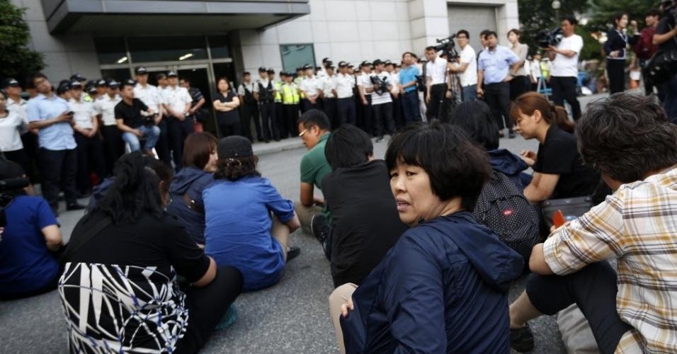 10.jun.2014 - Familiares dos passageiros que estavam a bordo da balsa Sewol se sentam em frente ao prédio onde membros da tripulação da balsa Sewol estão detidos, após participarem de audiência de pré-julgamento de 15 tripulantes, quatro deles acusados de homicídios, pelo naufrágio que matou mais 300 pessoas em Seul, na Coreia do Sul