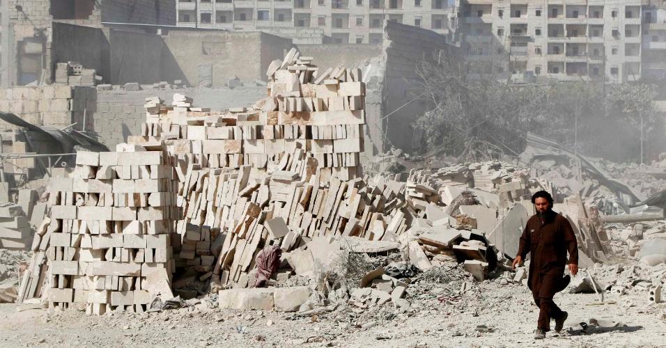 10.jun.2014 - Sírio caminha por escombros de edifícios danificados em local atingido, segundo rebeldes, por uma bomba de barril lançada por avião das forças leais ao ditador Bashar al-Assad, em Aleppo, nesta terça-feira (10)