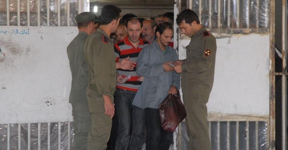 11.jun.2014 - Homens deixam presídio em Damasco, na Síria. Segundo o Observatório Sírio de Direitos Humanos, mais de 70 mil presos serão libertados nos próximos dias com o indulto ordenado pelo presidente sírio, Bashar al Assad, após sua reeleição no pleito da semana passada