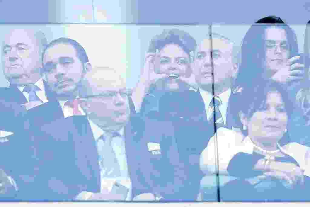 12.jun.2014 - 12.jun.2014 - A presidente Dilma Rousseff faz figa durante o jogo entre Brasil e Croácia na abertura da Copa do Mundo, na Arena Corinthians, em São Paulo. Na foto aparecem também o presidente da Fifa, Joseph Blatter (esq.) e o vice-presidente Michel Temer, (dir., na frente de Dilma). Parte do público presente no estádio xingou a presidente no momento em que era prevista uma homenagem aos operários que trabalharam nas obras dos 12 estádios do Mundial. A seleção brasileira começou perdendo por 1 a 0, mas virou o placar e venceu a partida por 3 a 1 - Piervi Fonseca/AGIF