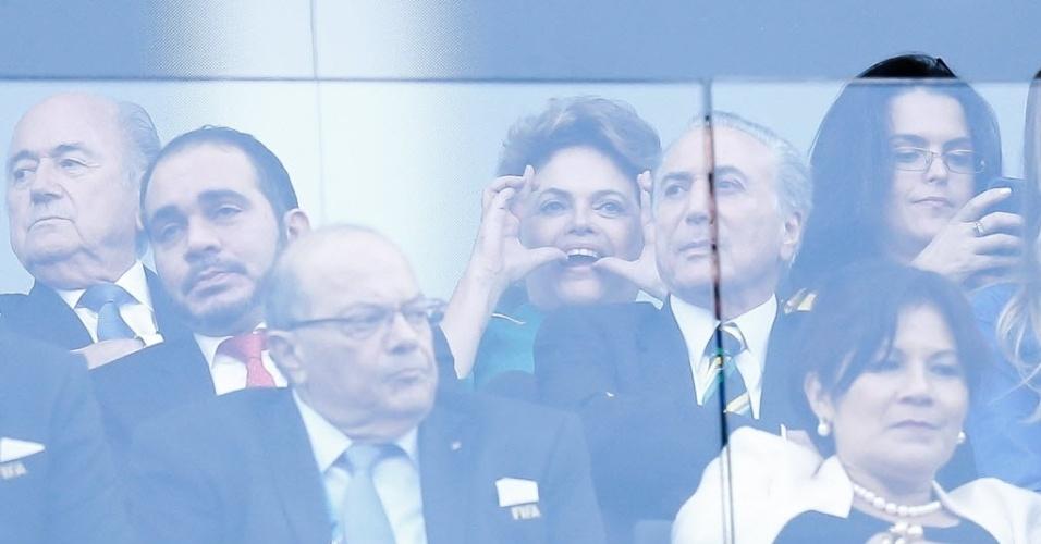12.jun.2014 - 12.jun.2014 - A presidente Dilma Rousseff faz figa durante o jogo entre Brasil e Croácia na abertura da Copa do Mundo, na Arena Corinthians, em São Paulo. Na foto aparecem também o presidente da Fifa, Joseph Blatter (esq.) e o vice-presidente Michel Temer, (dir., na frente de Dilma). Parte do público presente no estádio xingou a presidente no momento em que era prevista uma homenagem aos operários que trabalharam nas obras dos 12 estádios do Mundial. A seleção brasileira começou perdendo por 1 a 0, mas virou o placar e venceu a partida por 3 a 1