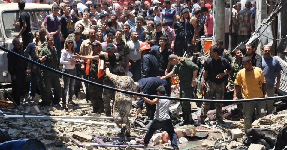 12.jun.2014 - Moradores observam local onde um carro-bomba explodiu em Wadi Dahab, no centro da cidade de Homs, na Síria, nesta quinta-feira (12). Ao menos sete pessoas morreram por causa do atentado