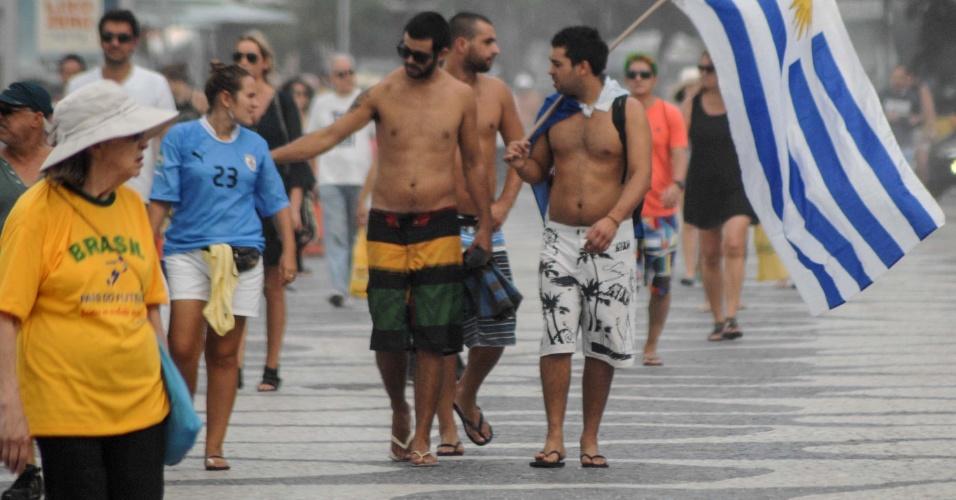 12.jun.2014 - Torcedores uruguaios caminham no calçadão da praia de Copacabana, no Rio de Janeiro, momentos antes do início do jogo de estreia da Copa do Mundo entre brasil e Croácia, que ocorre na Arena Corinthians, em São Paulo