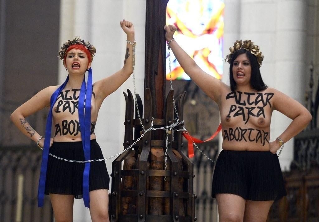 13.jun.2014 - Ativistas do Femen (grupo feminista famoso pelos protestos com o uso de topless) se acorrentam a uma cruz na catedral Almudena, em Madri, em manifestação contra a reforma de lei que restringiria o direito ao aborto na Espanha. A proposta elaborada pelo governo do país ainda não foi votada no Parlamento