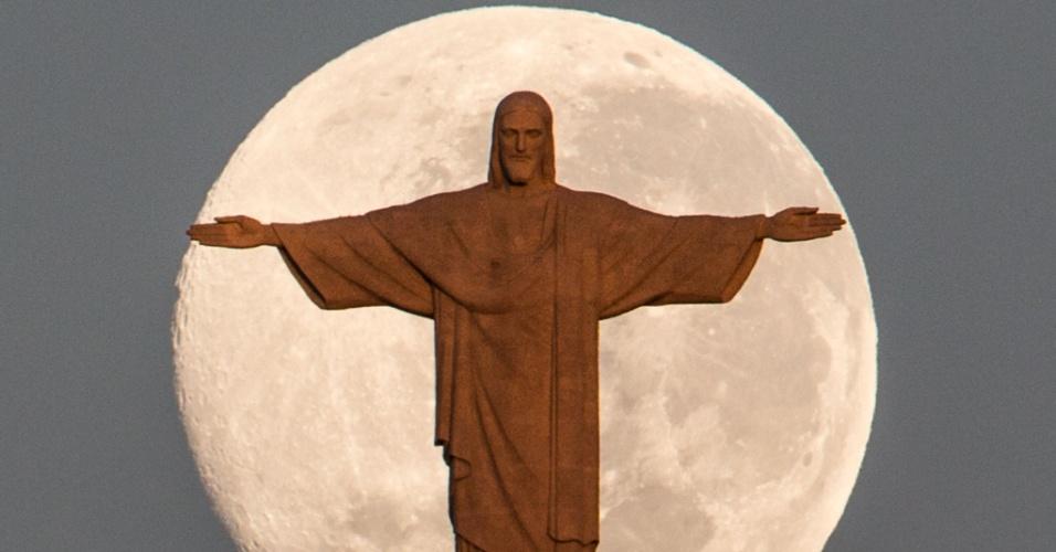 14.jun.2014 - Cristo Redentor, no Rio de Janeiro, é fotografado no exato momento em que a lua se encontrava 'atrás' do monumento, na madrugada deste sábado (14)