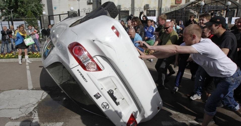14.jun.2014 - Manifestantes ucranianos viram carro em frente à embaixada russa em Kiev, neste sábado (14). Proteste pede para que o presidente da Rússia, Vladimir Putin, pare de apoiar grupos separatistas no leste da Ucrânia