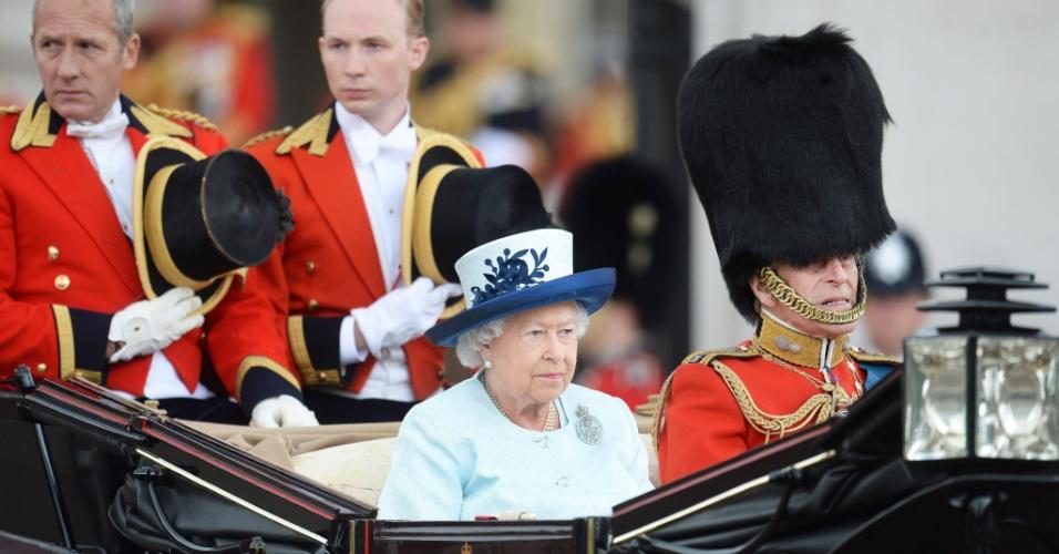 14.jun.2014 - Rainha Elizabeth 2ª e o príncipe Philip desfilam em carruagem aberta durante uma parada anual em homenagem ao aniversário da chefe de estado britânica em Londres, Reino Unido. Além da rainha e do príncipe Philip, outros integrantes da família real participaram da cerimônia com o príncipe William e sua esposa, Kate Middleton