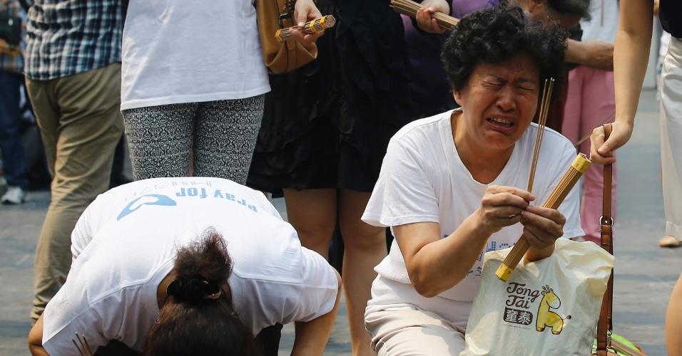 15.jun.2014 - Parentes de passageiros do voo MH370 oram em Pequim, na China, neste domingo, que marca o 100º dia de desaparecimento do avião. A aeronave seguia de Kuala Lumpur para Pequim com 239 pessoas a bordo