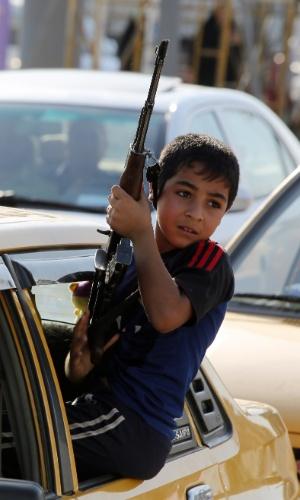 16.jun.2014 - Um garoto iraquiano segura uma arma sentado na janela de um carro enquanto pessoas se aglomeram em ato para mostrar prontidão para ingressa nas forças de segurança do país e lutar contra os militantes jihadistas que tomaram diversas cidades do norte do Iraque, nesta segunda-feira (16), em Bagdá. Insurgentes sunitas assumiram no domingo (15) o controle de uma cidade no noroeste do Iraque de maioria turcomana, após um pesado tiroteio