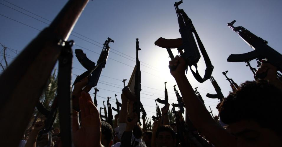 17.jun.2014 - Membros de tribos xiitas erguem suas armas para demonstrar vontade de se juntar às forças de segurança iraquianas e lutar contra os militantes jihadistas que tomaram várias cidades do norte do país, nesta terça-feira (17), na cidade santuário xiita de Najaf, no sul do Iraque