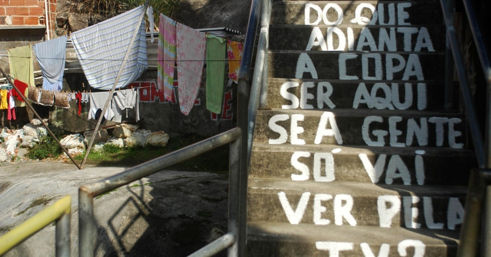 """17.jun.2014 - Moradores do morro Dona Marta, em Botafogo, zona sul do Rio de Janeiro, pintam as calçadas com frases de protesto contra a Copa do Mundo no Brasil. """"Fifa Go Home"""", """"Copa Pra Quem?"""" e """"Mais escolas, menos estádios"""" eram frases que podiam ser lidas no local"""