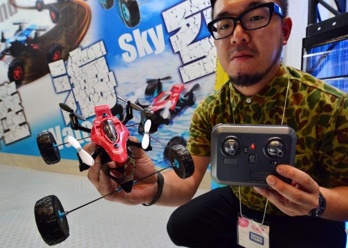 Funcionário da empresa japonesa Tomy exibe veículo anfíbio controlado por rádio (ele se locomove tanto em terra como na água e também no ar). A página oficial da empresa não divulga informações sobre preço ou disponibilidade do produto