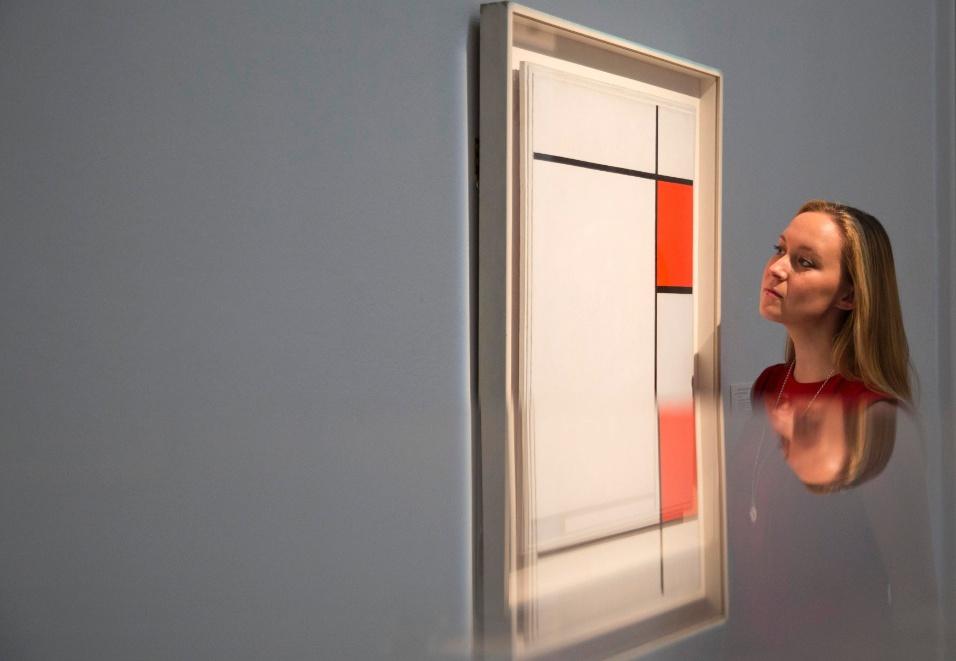 """18.jun.2014 - Assistente de galeria observa o trabalho """"Composição em Vermelho, Azul e Cinza"""", de Piet Mondrian"""