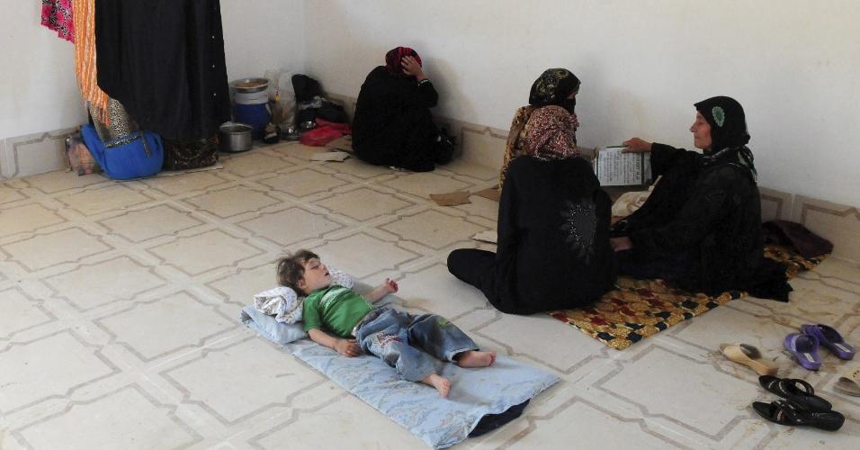 18.jun.2014 - Família iraquiana se aloja em campo de refugiados próximo da cidade de Mosul, no norte do país, nesta quarta-feira (18). Mais de dois milhões de iraquianos se ofereceram como voluntários para lutar contra os militantes do grupo jihadista Exército Islâmico do Iraque e do Levante (EIIL)