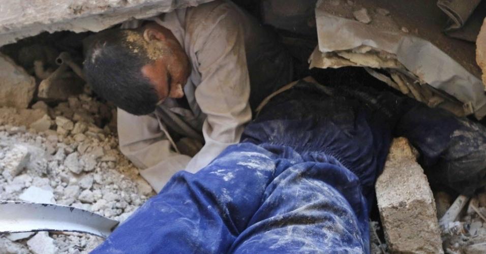18.jun.2014 - Homem tenta resgatar uma pessoa que ficou presa sob os escombros de edifícios derrubados por um ataque a bomba, realizado por forças leais ao ditador Bashar Assad, em Aleppo, Síria