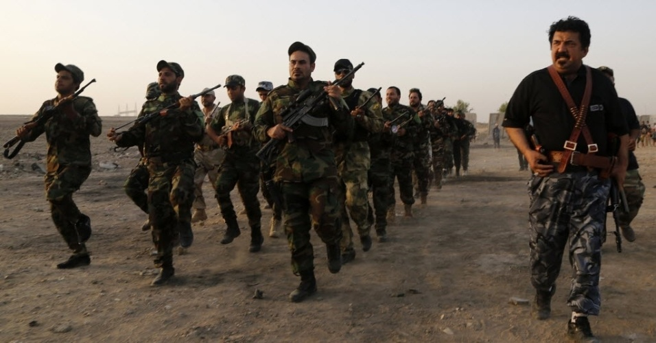 18.jun.2014 - Soldados do Exército Mehdi leais ao clero xiita Moqtada al-Sadr marcham durante um treinamento militar em Bagdá, nesta quarta-feira (18). O Iraque solicitou apoio aéreo aos Estados Unidos para combater rebeldes sunitas nesta quarta-feira (18), depois que militantes ocuparam grandes cidades em um avanço-relâmpago contra o Exército do governo liderado por xiitas