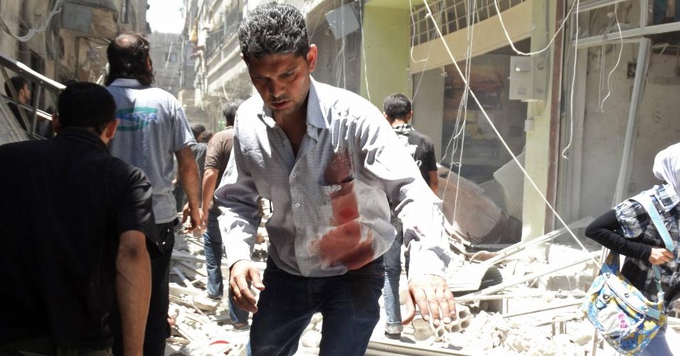 18.jun.2014 - Um homem com marcas de sangue na camisa caminha entre destroços em local onde aconteceu um ataque aéreo supostamente realizado por forças leais ao ditador sírio Bashar al-Assad, no subúrbio de Saqba, em Damasco, nesta quarta-feira (18)