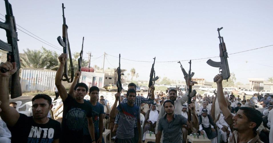 18.jun.2014 - Voluntários xiitas mostram armas em Kerbala, no sul do Iraque, nesta quarta-feira (18). Mais de dois milhões de iraquianos se ofereceram como voluntários para lutar contra os militantes do grupo jihadista Exército Islâmico do Iraque e do Levante (EIIL)