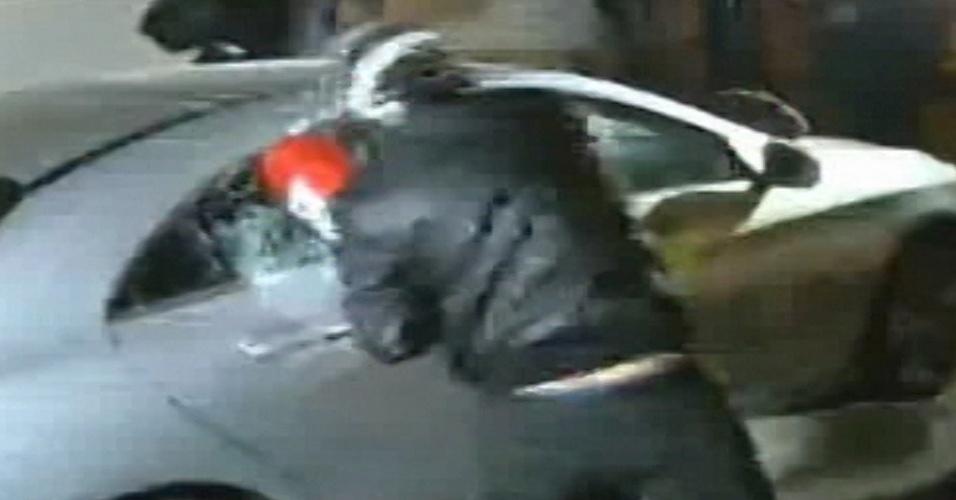 19.jun.2014 - Manifestante quebra vidros de um carro de luxo dentro de uma concessionária durante protesto nesta quinta-feira (19). O protesto convocado pelo Movimento Passe Livre terminou em violência após os manifestantes terem fechado a Marginal Pinheiros