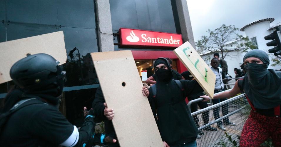 19.jun.2014 - Manifestantes mascarados impedem outros de depredarem agência bancária na avenida Rebouças, zona oeste de São Paulo
