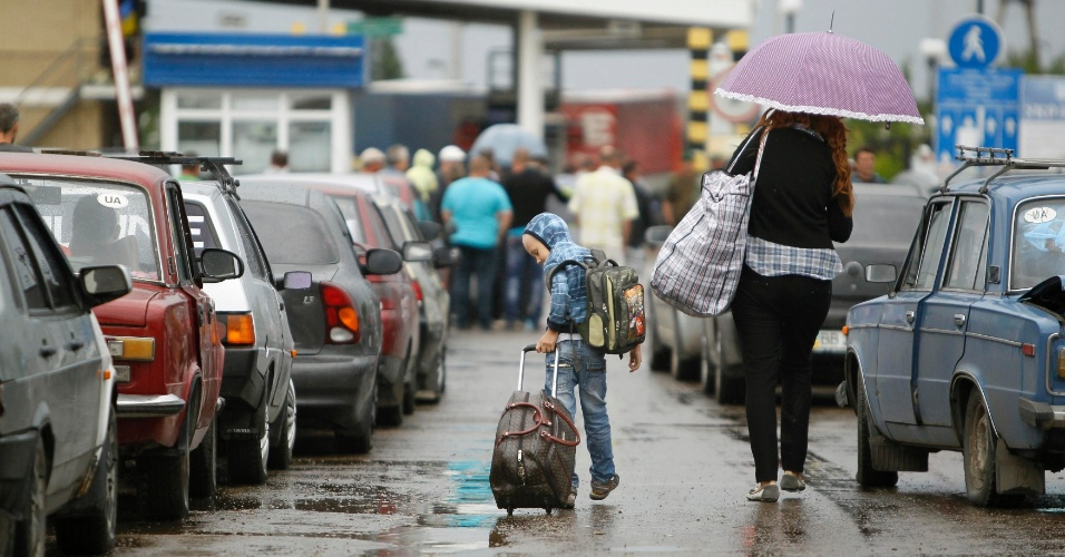 20.jun.2014 - Pessoas caminham até o posto de fronteira de Izvaryne, na fronteira com a Rússia, nesta sexta-feira (20). O governo da Ucrânia anunciou um cessar-fogo unilateral nos combates contra separatistas no leste do país
