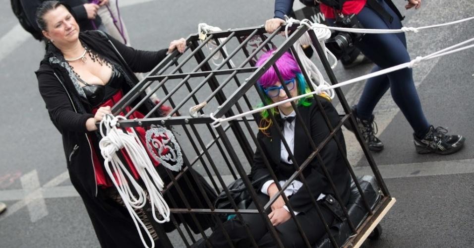 21.jun.2014 - Uma mulher é carregada dentro de uma jaula durante a Parada do Orgulho Gay em Berlim neste sábado (21). Há 35 anos a parada é realizada em Berlim, mas, neste ano, pela primeira vez, ela foi dividida em duas correntes. Na imagem, as participantes são da nova vertente, chamada