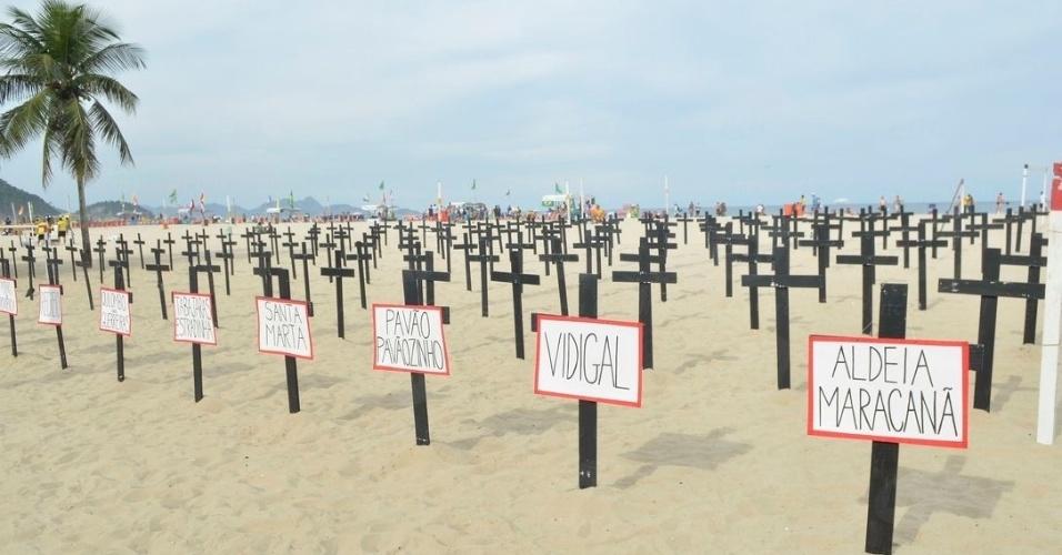 23.jun.2014 - Cruzes foram colocadas na praia de Copacabana por representantes de várias comunidades do Rio de Janeiro, na manhã desta segunda-feira (23), em um protesto contra as remoções de moradias feitas para a Copa do Mundo, o déficit habitacional e as políticas habitacionais no país