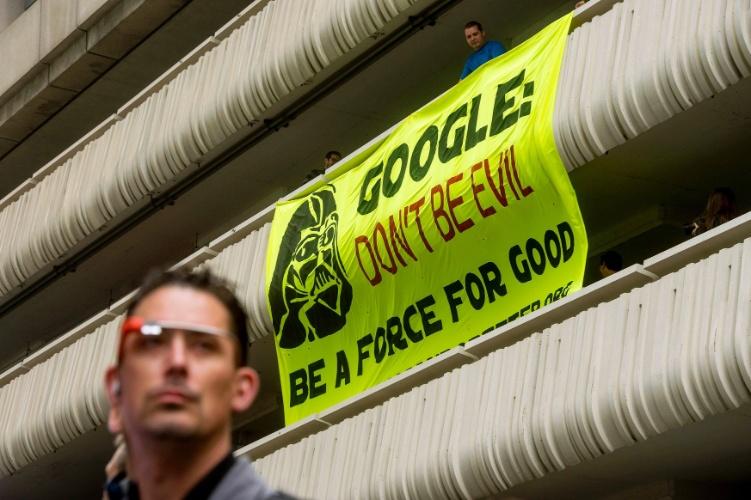 """25.jun.2014 - Manifestante segura cartaz na cidade de San Francisco, na Califórnia (EUA), em frente ao local onde é realizado o Google I/O, um evento para desenvolvedores da empresa de buscas. A mensagem escrita no cartaz é: """"Google não seja mal. Que a força esteja você"""". Companhias de tecnologia, como o Google, têm sido alvo de protestos em função do crescimento do despejo de moradores, ocasionado pelos altos salários de companhias da área de tecnologia da informação"""