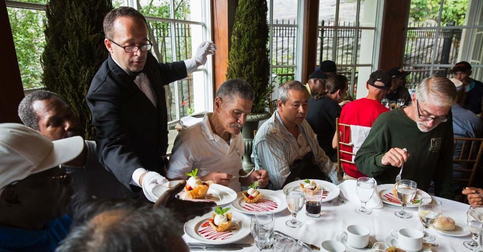 Garçom serve sobremesa a convidados, durante almoço oferecido pelo bilionário chinês Chen Guangbiao a pessoas carentes em Nova York, nos EUA