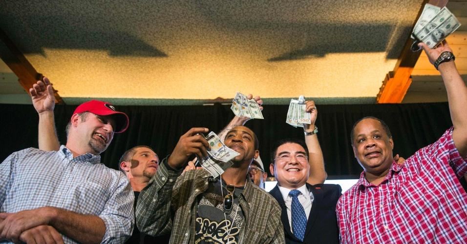 O bilionário chinês Chen Guangbiao posa ao lado de homens que receberam US$ 300 durante almoço oferecido pelo magnata para pessoas carentes