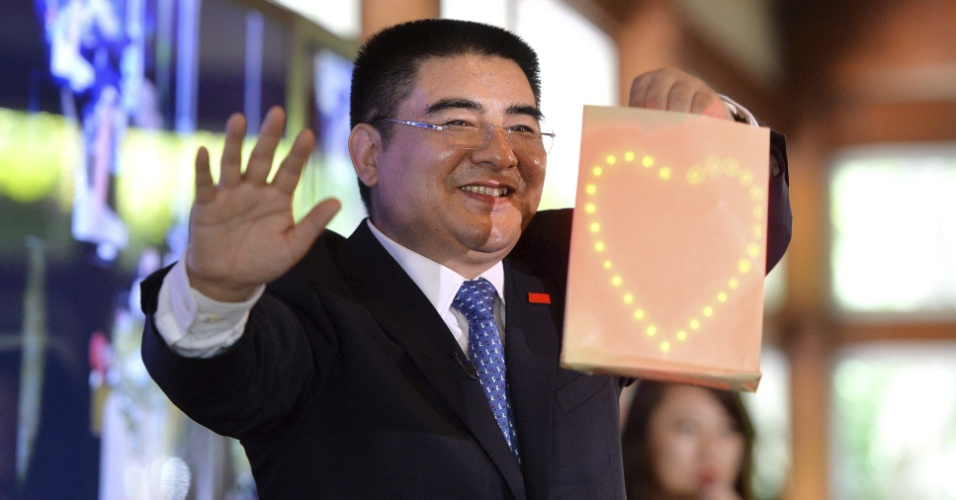 O chinês Chen Guangbiao, empresário do ramo de demolições, faz um truque de mágica para convidados