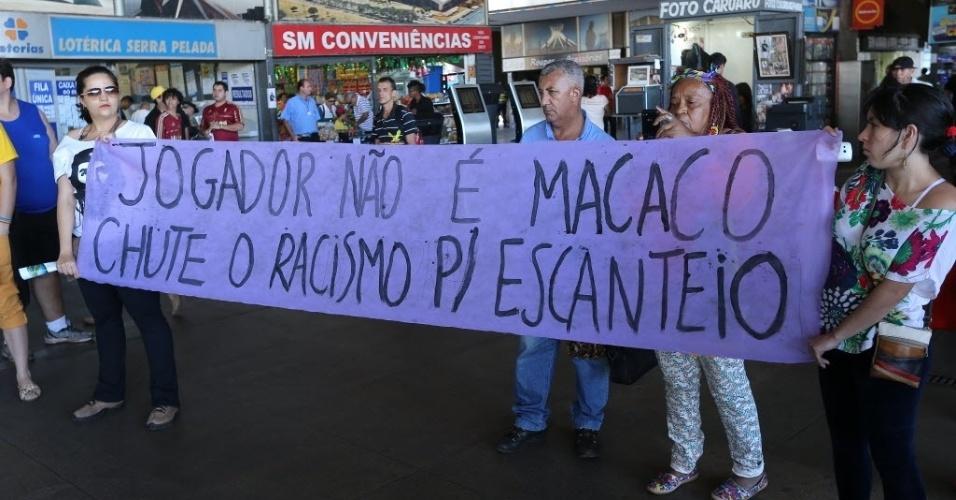 """26.jun.2014 - Manifestantes erguem faixa onde se lê """"Jogador não é macaco, chute o racismo para escanteio"""", durante protesto contra a Copa do Mundo, homofobia e pelo direito das mulheres, realizado pelo movimento """"Copa das Manifestações"""", nesta quinta-feira (26), em Brasília"""