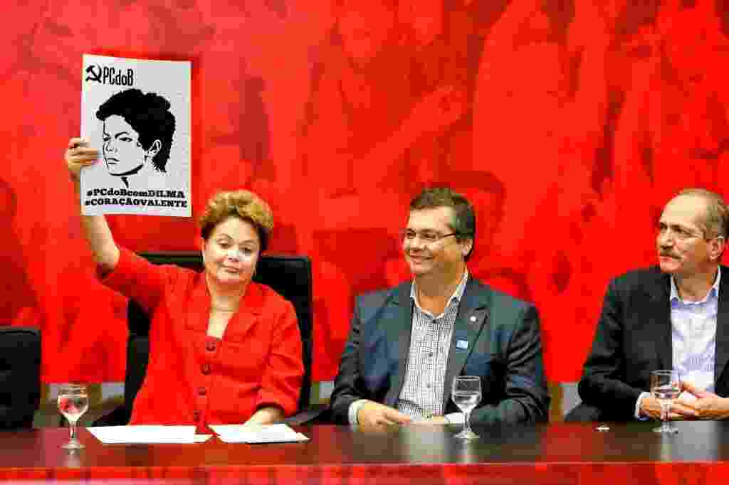27.jun.2014 - A presidente Dilma Rousseff ergue cartaz com a foto dela feita na ocasião de seu julgamento pelo tribunal militar na época da ditadura, onde escreveu uma mensagem destinada à UJS (União da Juventude Socialista), durante a convenção nacional do PC do B, nesta sexta-feira (27). Na ocasião, o partido ratificou o apoio à reeleição da presidente. Ao lado de Dilma estão o candidato ao governo do Maranhão Flávio Dino (esq.), e o ministro do Esporte, Aldo Rebelo (dir) - Pedro Ladeira/Folhapress