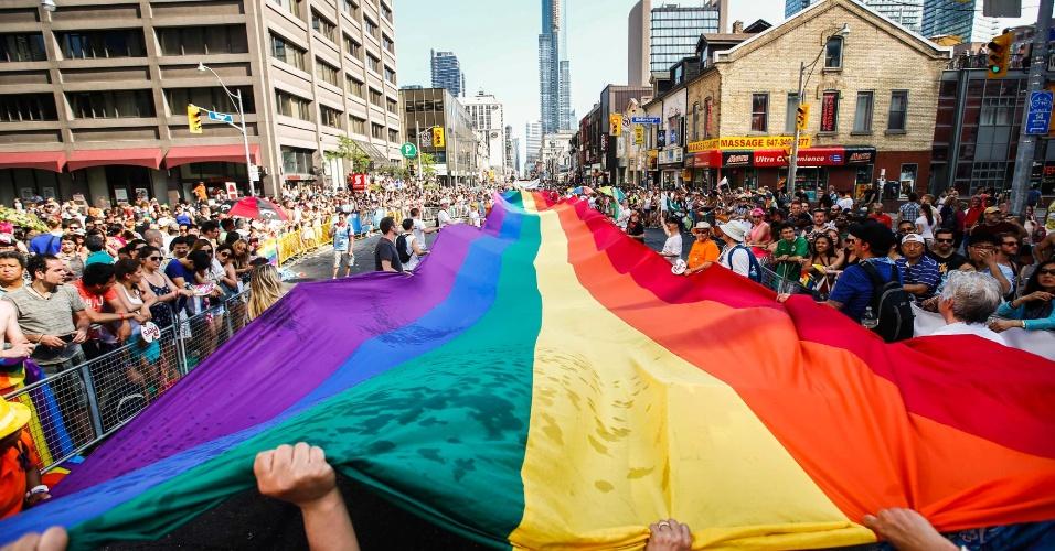 29.jun.2014 - Ativistas seguram uma bandeira gigante do orgulho gay durante parada gay em Toronto, no Canadá, neste domingo (29). Toronto abriga a WoldPride, uma semana inteira de eventos voltados para a comunidade LGBT