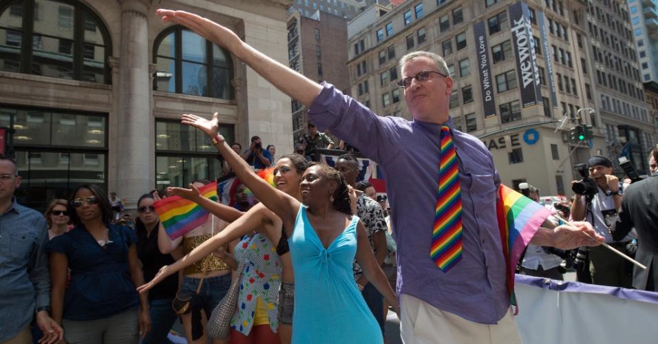 29.jun.2014 - O prefeito de Nova York, Bill de Blasio, usa uma gravata coloridade e dança ao lado da primeira-dama, Chirlane McCray, e de Chiara de Blasio, durante Parada do Orgulho Gay, no bairro de Manhattan, em Nova York, neste domingo (29)