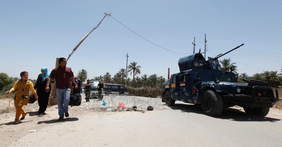30.jun.2014 - Iraquianos observam tanque de guerra usado no reforço da segurança em Bagdá. Prováveis ataques sunitas de integrantes do Estado Islâmico do Iraque e do Levante  (EIIL)  motivaram o reforço da segurança na região da capital iraquiana
