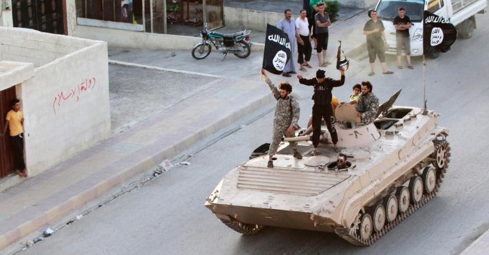 30.jun.2014 - Militantes islamitas em um tanque participam de uma parada militar nas ruas ao norte da província de Raqqa, na Síria. Os rebeldes celebraram sua declaração de criação de uma califado islâmico, após o grupo ter capturado um território no Iraque. O Estado Islâmico, ligado à Al Qaeda conhecido anteriormente como Estado Islâmico no Iraque e o Levante (ISIL), o grupo postou fotos neste domingo (29)