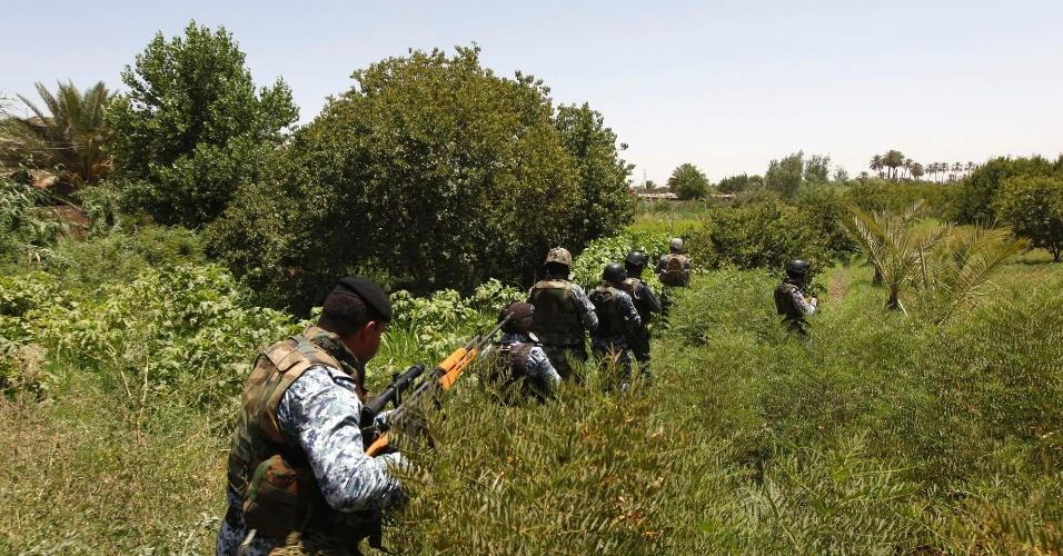 30.jun.2014 - Policiais iraquianos cruzam mata durante operação de busca por armar ilegais em Bagdá.