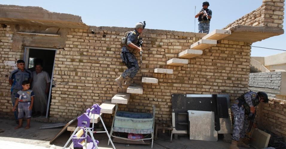 30.jun.2014 - Policiais iraquianos vasculham casa em operação de busca por armas em residência de Bagdá