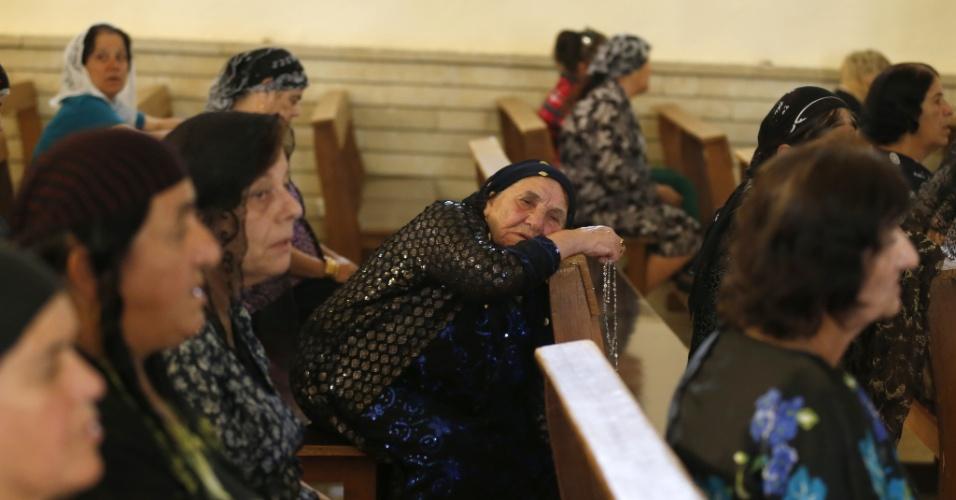 1º.jul.2014 - Iraquianas cristãs mostram desânimo ao rezar em igreja de Mosul, no norte do Iraque