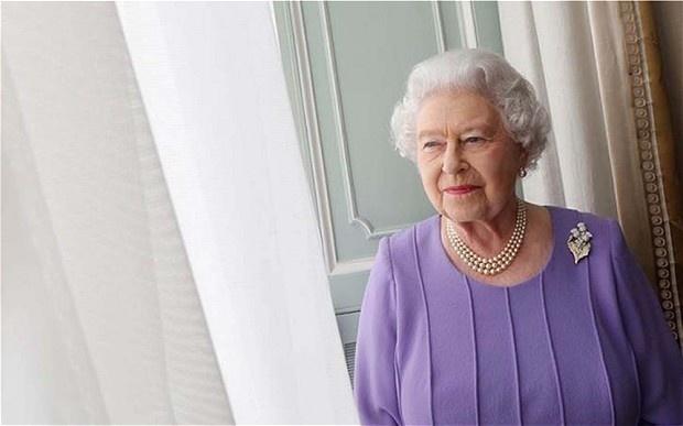 2.jul.2014 - A rainha Elizabeth 2ª parece distraída, apenas esboçando um meio sorriso enquanto olha com os olhos entreabertos pela janela do palácio, em seu último retrato oficial divulgado na terça-feira (1º) e que leva a assinatura do veterano Harry Benson