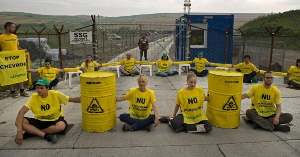 7.jul.2014 - Ativistas do Greenpeace bloqueiam a entrada do poço de exploração de gás de xisto da empresa americana Chevron, na vila de Pungesti, na Romênia, nesta segunda-feira (7). 25 ativistas sentaram em frente à entrada do local e exibiram cartazes contra a técnica de extração de gás, que injeta água misturada com produtos químicos no solo