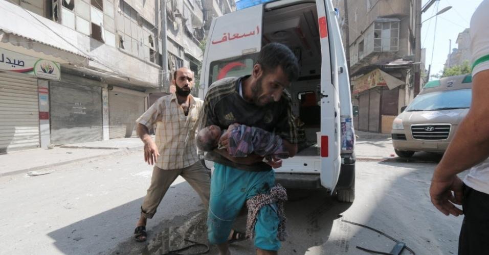 9.jul.2014 - Homem corre carregando um bebê no bairro oriental de Shaar, da cidade de Aleppo, nesta quarta-feira (9), depois que quatro barris de bombas foram lançados pela força aérea síria, danificando casas e lojas