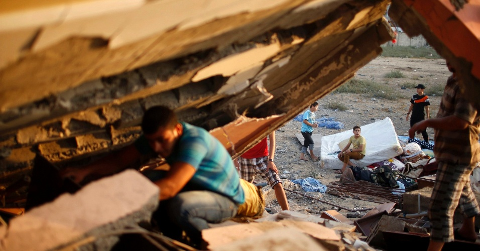 9.jul.2014 - Palestino procura por pertences sob os escombros de casa destruída, segundo a polícia, em um ataque aéreo israelense na cidade de Gaza, nesta quarta-feira (9). Pelo menos 23 pessoas foram mortas em toda faixa de Gaza em bombardeios que podem ser apenas o início de uma ofensiva prolongada contra o Hamas, a maior desde 2012, após novos foguetes palestinos atingirem Israel