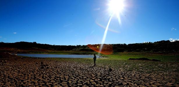 Pescador caminha sobre terra seca na barragem Jaguari, do Sistema Cantareira, na crise hídrica de 2014
