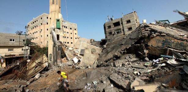 Palestino anda por destroços da mesquita Al-Tawfeeq após ataque aéreo no campo de refugiados Al-Nusairat, no centro da faixa de Gaza