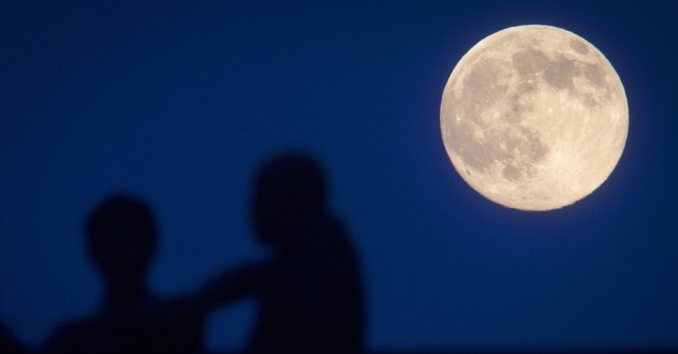 12.jul.2014 - Pessoas observam Superlua em ponte de Manhattan, em Nova York. Os cientistas usam essa denominação para explicar o momento em que a Lua está mais próxima da Terra e parece maior e mais brilhante